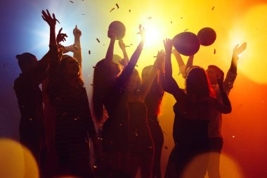 A crowd of people in silhouette raises their hands against colorful neon light on party background