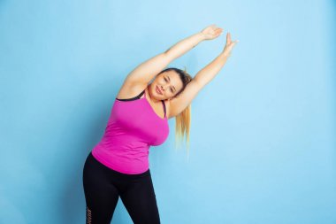 Young caucasian plus size female models training on blue background