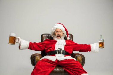 Santa Claus drinking beer sitting on armchair, congratulating of New Year 2020