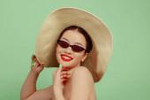 Portrét krásné mladé ženy s jasným make-up izolované na zeleném pozadí studia