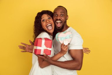 Holding giftboxes. Valentines day celebration, happy african-american couple isolated on yellow studio background. Concept of human emotions, facial expression, love, relations, romantic holidays. stock vector
