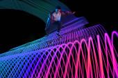 Kavkazský mladý skateboardista na temném neonovém osvětleném pozadí