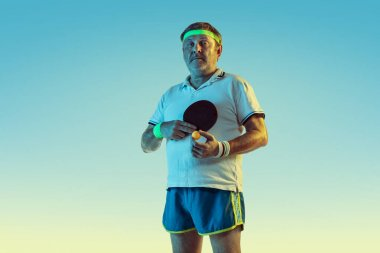 Senior man playing table tennis in sportwear on gradient background and neon light