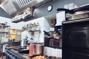 Behind the scenes of brands. The chef cooking in a professional kitchen of a restaurant meal for client or delivery. Motion.