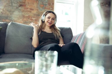 Young woman wearing wireless headphones gesturing during a video conference in the living room. Waving