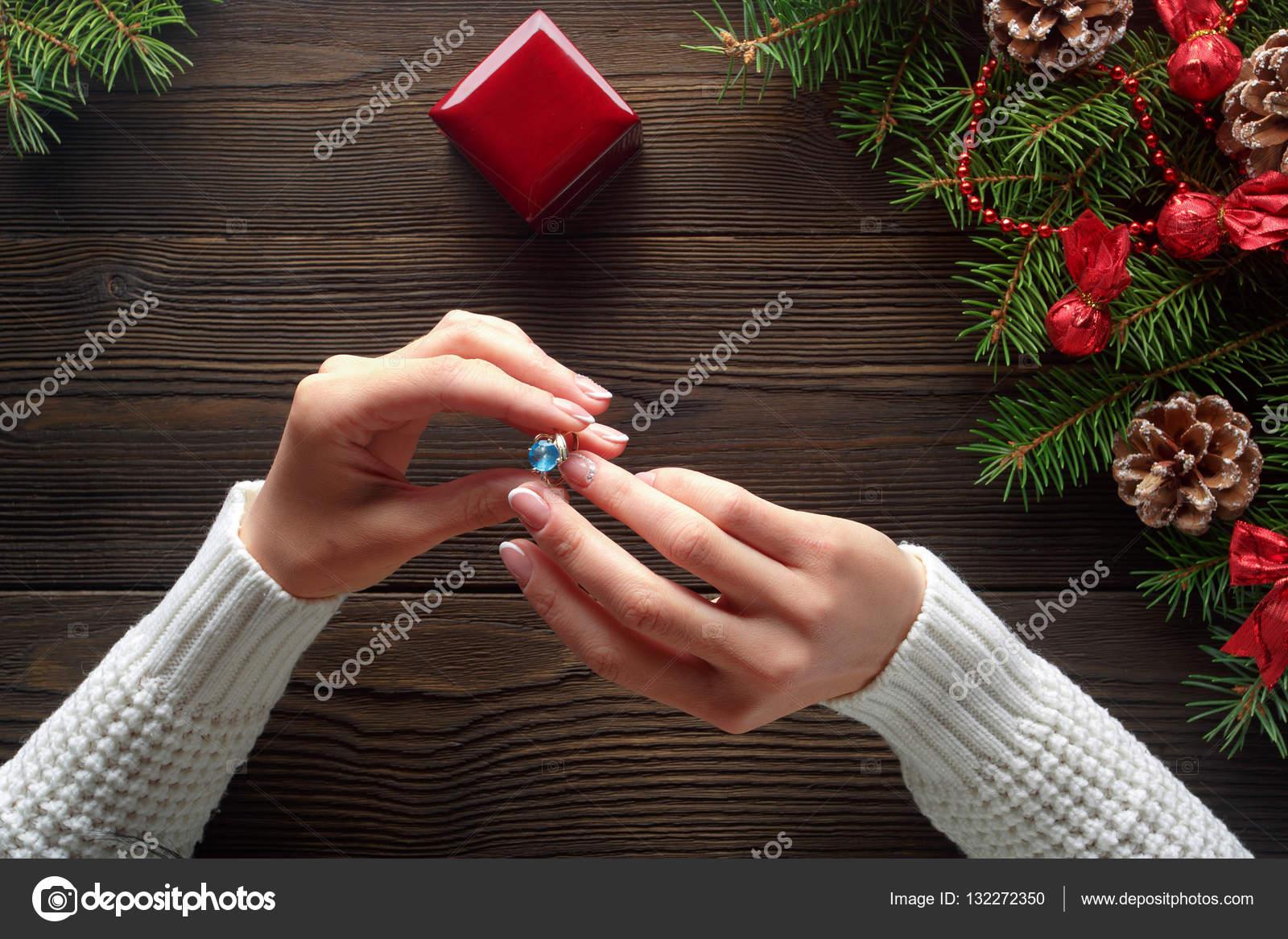 Verlobungsring In Weiblichen Handen Unter Weihnachtsschmuck Auf Holz