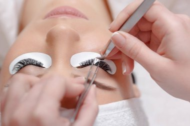 Eyelash Extension Procedure. Woman Eye with Long Eyelashes