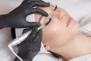 Cosmetologist making permanent makeup