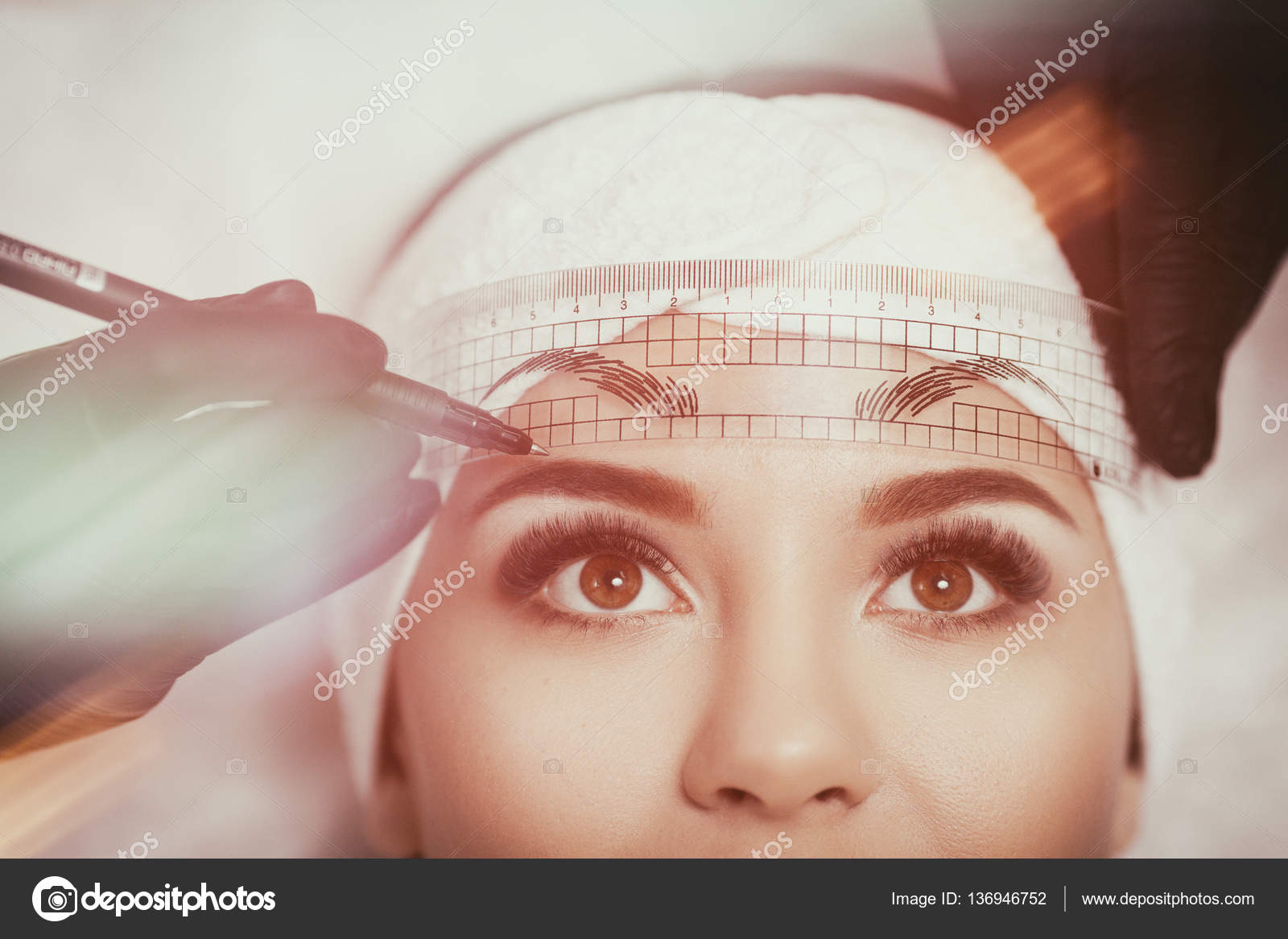Permanent makeup eyebrows. Mikrobleyding eyebrows workflow in a beauty salon. Cosmetologist applying a special permanent makeup on a womans eyebrows.