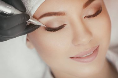 Cosmetologist making permanent make up at beauty salon