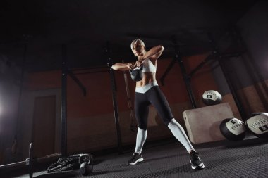 Muscular young fitness woman lifting a weight in the gym