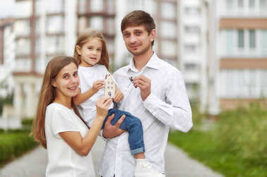 Happy family in front of new apartment building