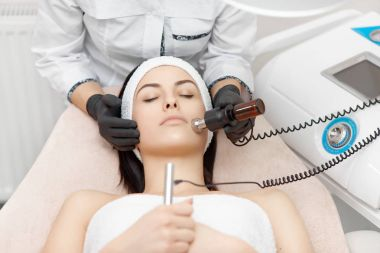 Beauty salon facial treatment with radio frequency machine.