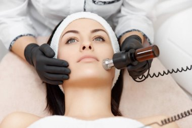 Beautiful woman enjoying rf lifting in beauty salon.