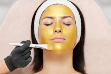 Cosmetologist applying gold mask on face of beautiful brunette.