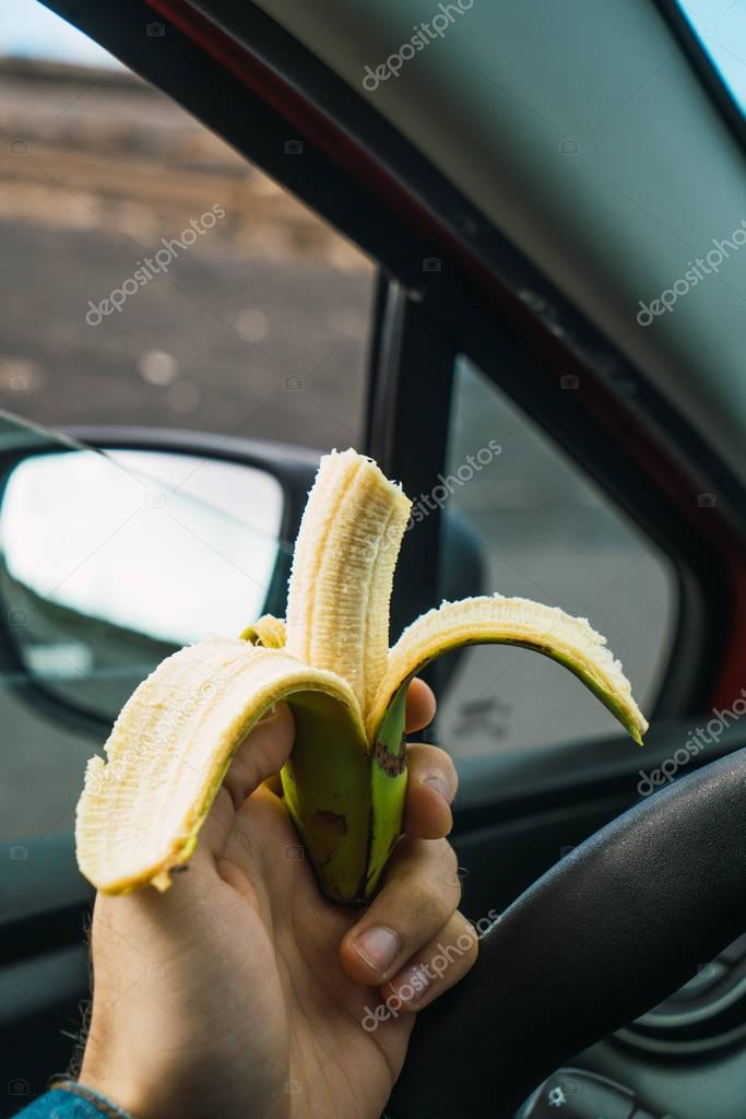 Person eating banana in car