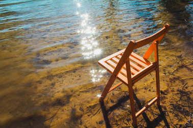 Chair in shallow water of lake