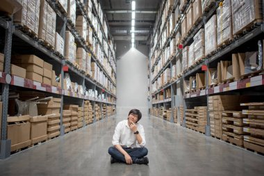 Young Asian man sitting in warehouse choosing what to buy