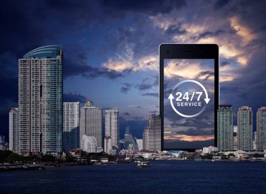 24/7 service flat icon on modern smart mobile phone screen over office city tower, skyscraper, river and sunset sky, Business full time online service concept