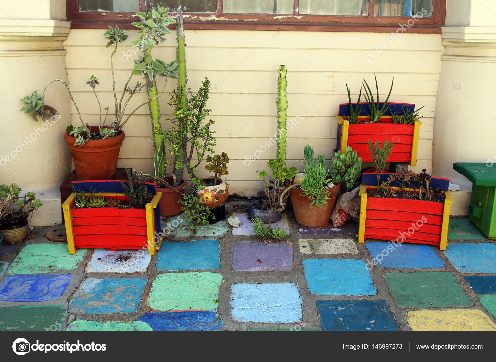 Scatole di legno colorati e vasi con piante e cactus su un