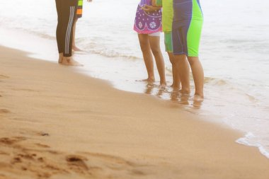 Children standing on sand beach at the sea.