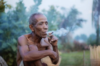 Yaşlı adam kırsalda sigara içiyor..