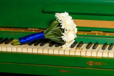 Beautiful and cute bridal bouquet lying on the piano. Wedding ri
