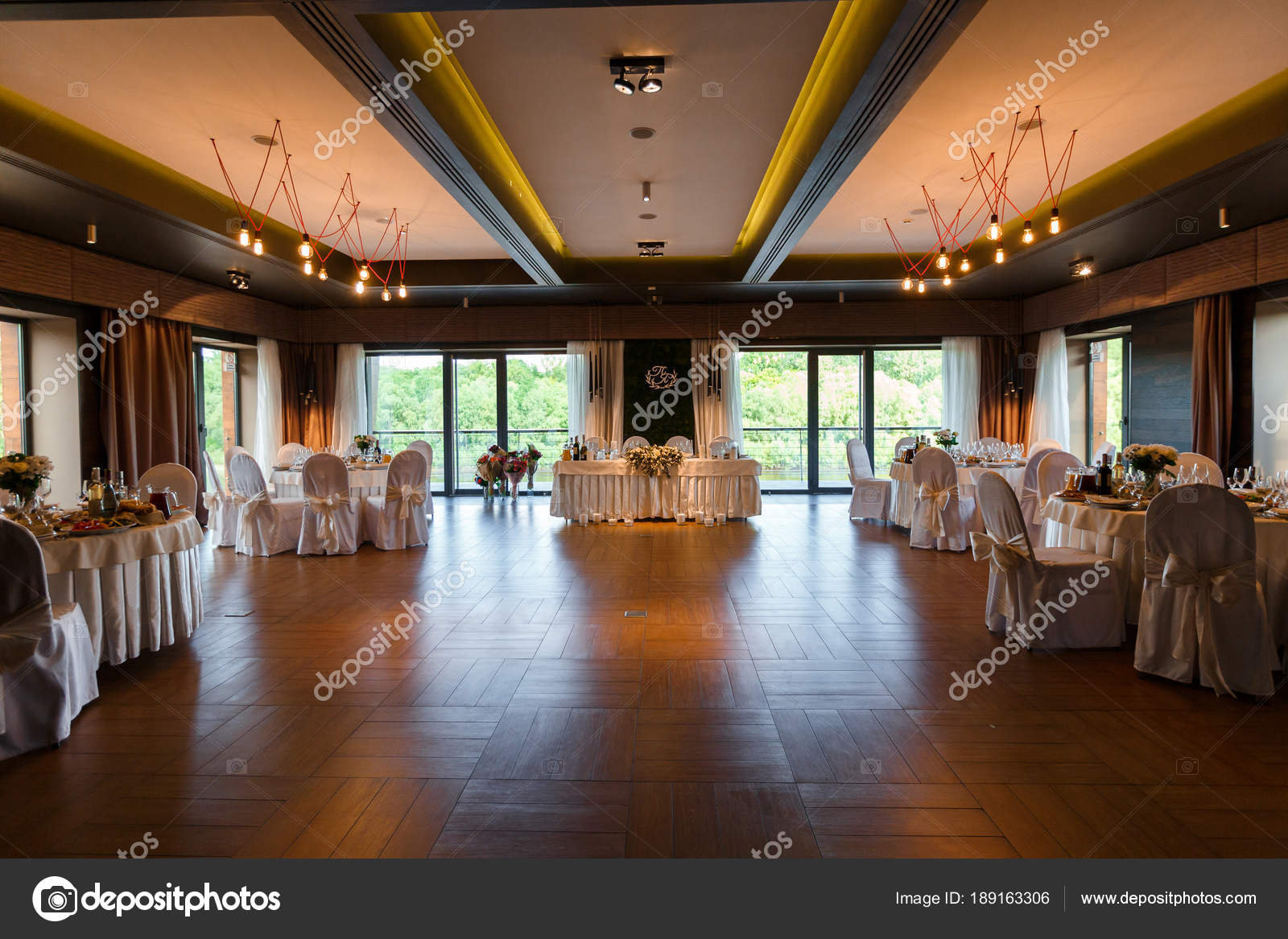 A modern banquet hall decorated with floristry. Wedding table de ...
