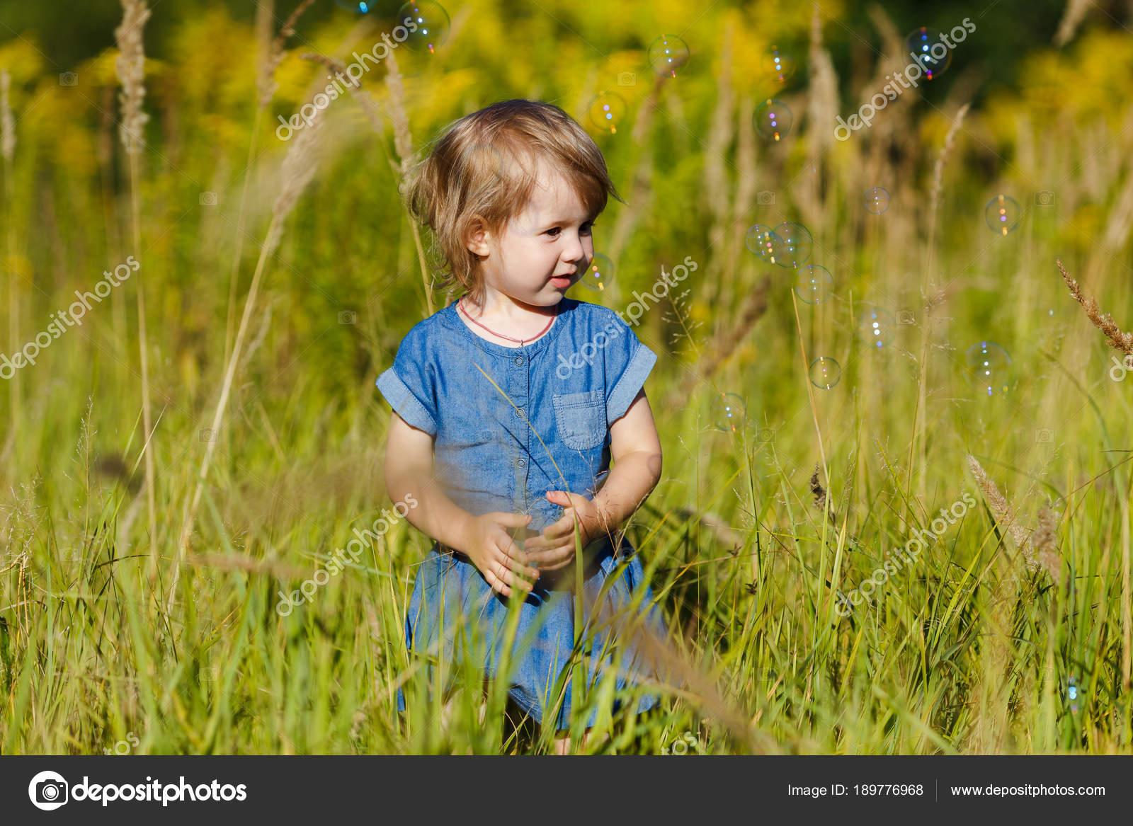 Una niña en vestido azul tratando de atrapar las burbujas de jabón ...