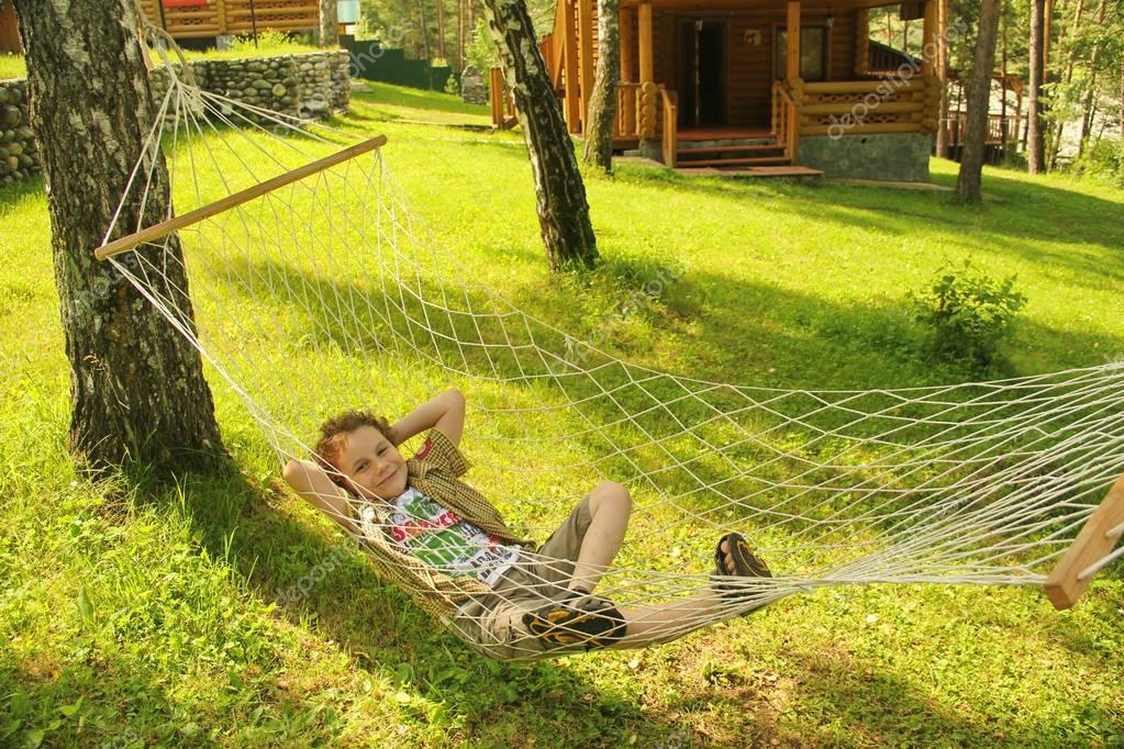 happy cheerful child smiling and lying, resting in a hammock in the woods in a glade in summer among the bright green grass
