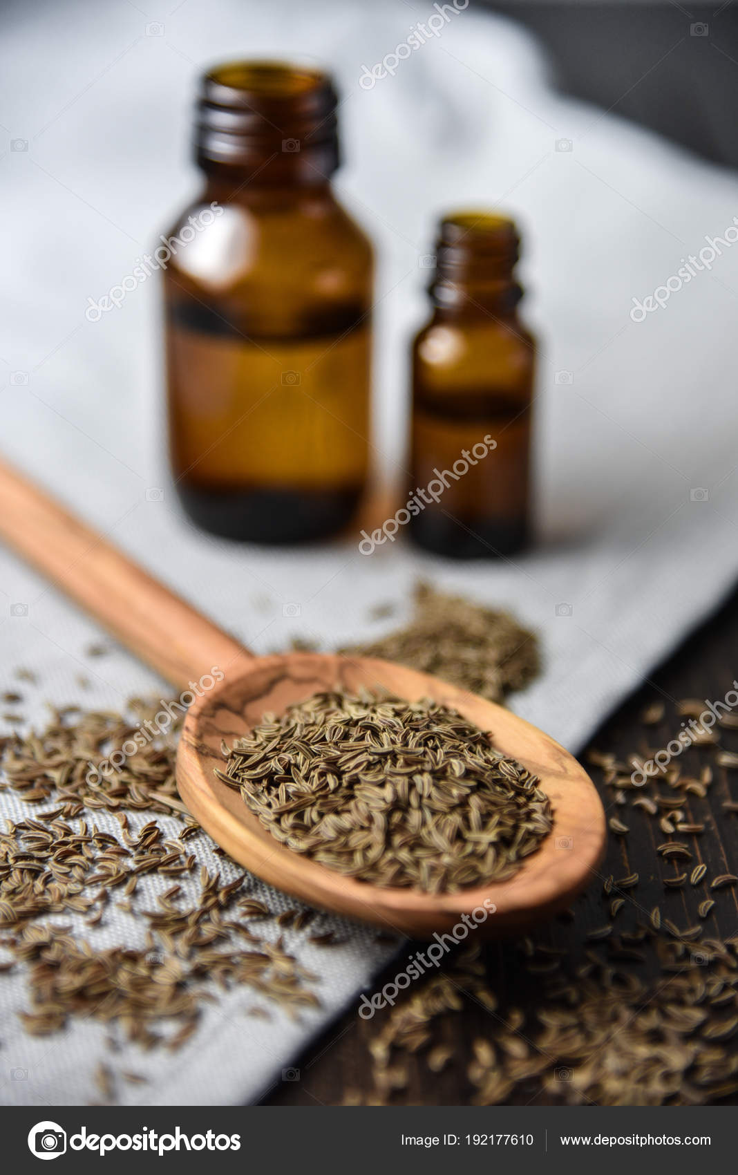 Caraway oil and seeds on wooden spoon and essential oil