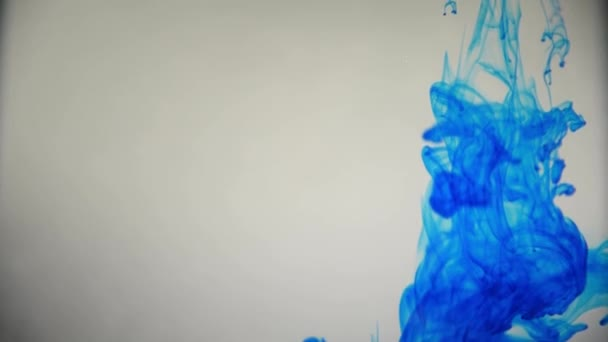 Blue color paint ink pouring over the glass with inky drops falling and abstract smoke explosion watercolors