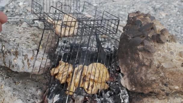 Mladý muž ve sportovním oblečení peče maso na grilu. Odpočívej v přírodě. Pal. Maso. Jídlo. Nůž. Hlad. Grilování. Přívěs. Přívěs.