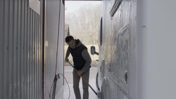 Ein junger Mann europäischer Staatsangehörigkeit wäscht ein Auto in einer Waschanlage. Selbstversorgung. Saisonale RV Freizeitmobil Wohnmobil Reinigung mit Hochdruckreiniger. Wohnmobil. Kaukasische Männer