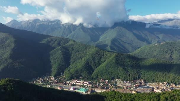 Légi felvétel. Kilátás a hegyekre. Kilátás fentről. Völgy. Vörös Poliána. Szocsit. Felhők a hegyek felett. Nincsenek emberek. Zöld fák.