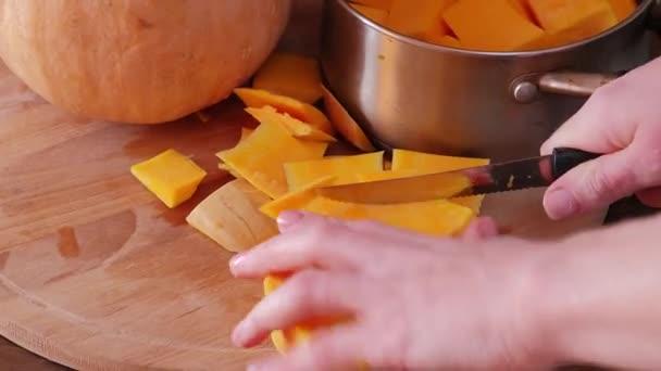 Dívka ruka řeže velké oranžové dýně na dřevěné desce izolované na černém pozadí. Halloween a Den díkůvzdání pojetí jídla. Zavřít