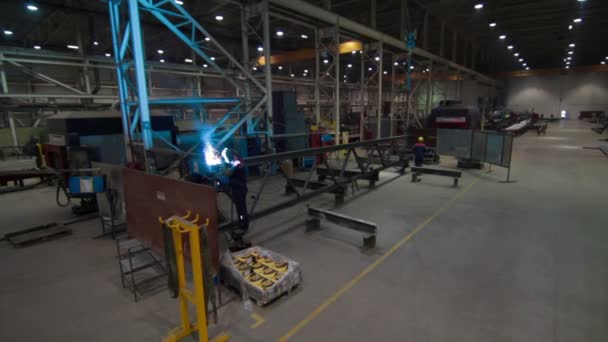 Workers grinding and welding steel bar in a factory