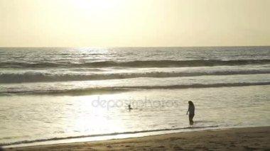 Surfer paddling over ocean wave at sunset in slow motion
