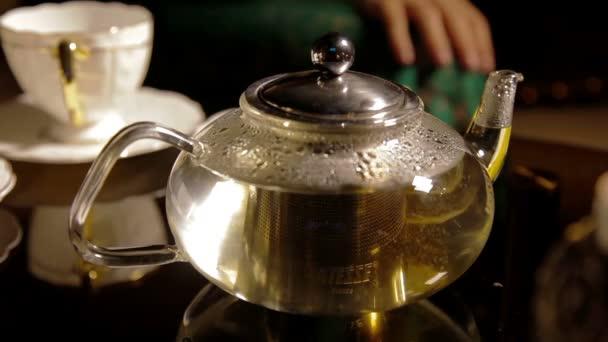 Čaj. Lití zdravý čaj. Konvice a šálek čaje sklo na stůl