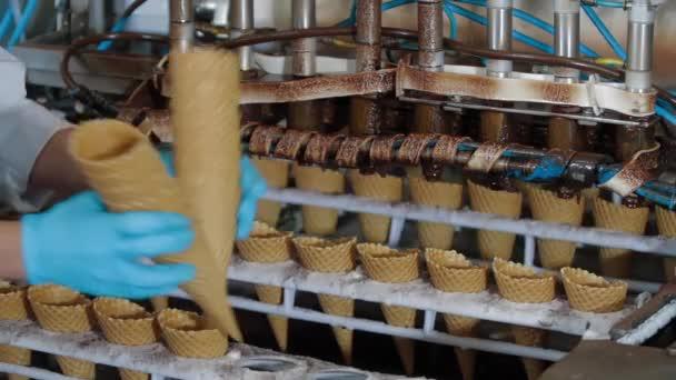 Robotický stroj Automaticky nalévá čokoládu do pohárků s oplatkami. Dopravníkové automatické linky pro výrobu zmrzlinových šišek. Oplatky a kornouty. Velká průmyslová výroba.