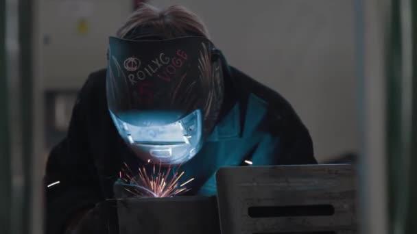 Detailní kovářská svářečka v ochranné masce pracuje s kovovou ocelí a železem pomocí svařovacího stroje, jasných jisker a záblesků. Svářeč používá masku, aby ochránil vaše oči před jiskrami.