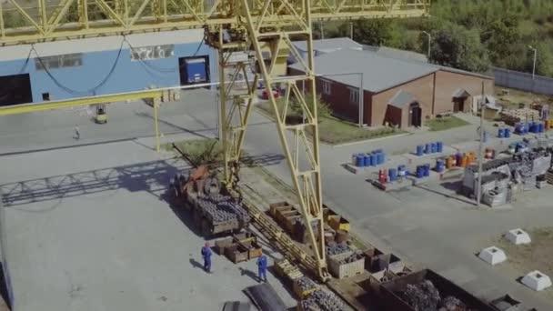 Letecký záběr průmyslového portálového jeřábu. Horní pohled na instalaci portálového jeřábu. Pracovní proces ve skladu s kovem. Pracovníci vyloží kov stojící pod portálovým jeřábem, dělníci na rampě.