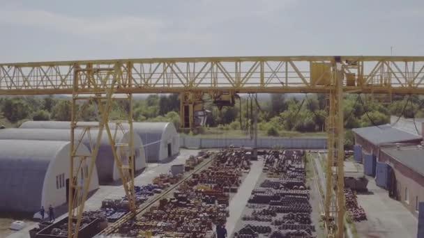 Letecký záběr průmyslového portálového jeřábu. Horní pohled na instalaci portálového jeřábu. Pracovní proces ve skladu s kovem. Pracovníci vyloží kov stojící pod portálovým jeřábem