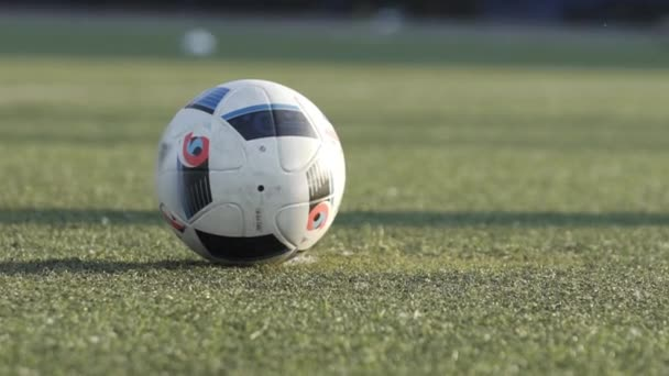 Close-up of footballer leg kicking soccer ball on outdoor football pitch. SLow motion of Soccer player training drills on an empty stadium football field.