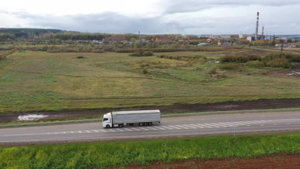 Aerial View of White Truck with Cargo Semi Trailer Moving on Road in Direction of Loading Warehouse Area. Large Delivery Truck is Moving. Aerial Shot Of Lorry On Road In Beautiful Countryside.