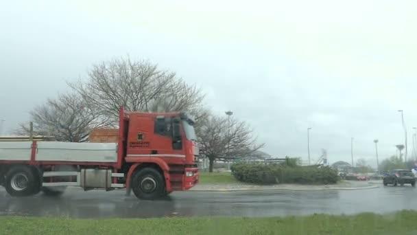 Zpomalený pohyb. Panoramatický pohled červené nákladní vůz prochází kruhový objezd. Deštivý den, špatné počasí, nastavení