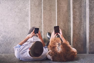 Man with woman standing on stairs with phones