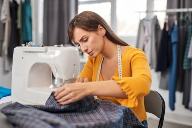 Focused charming caucasian fashion designer sitting in her studio and sewing beautiful evening dress.