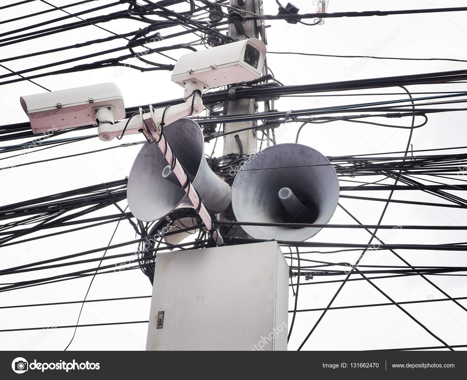 cctv camera security and vintage horn speaker with cables and wires on pole  / white background — photo by vichailao
