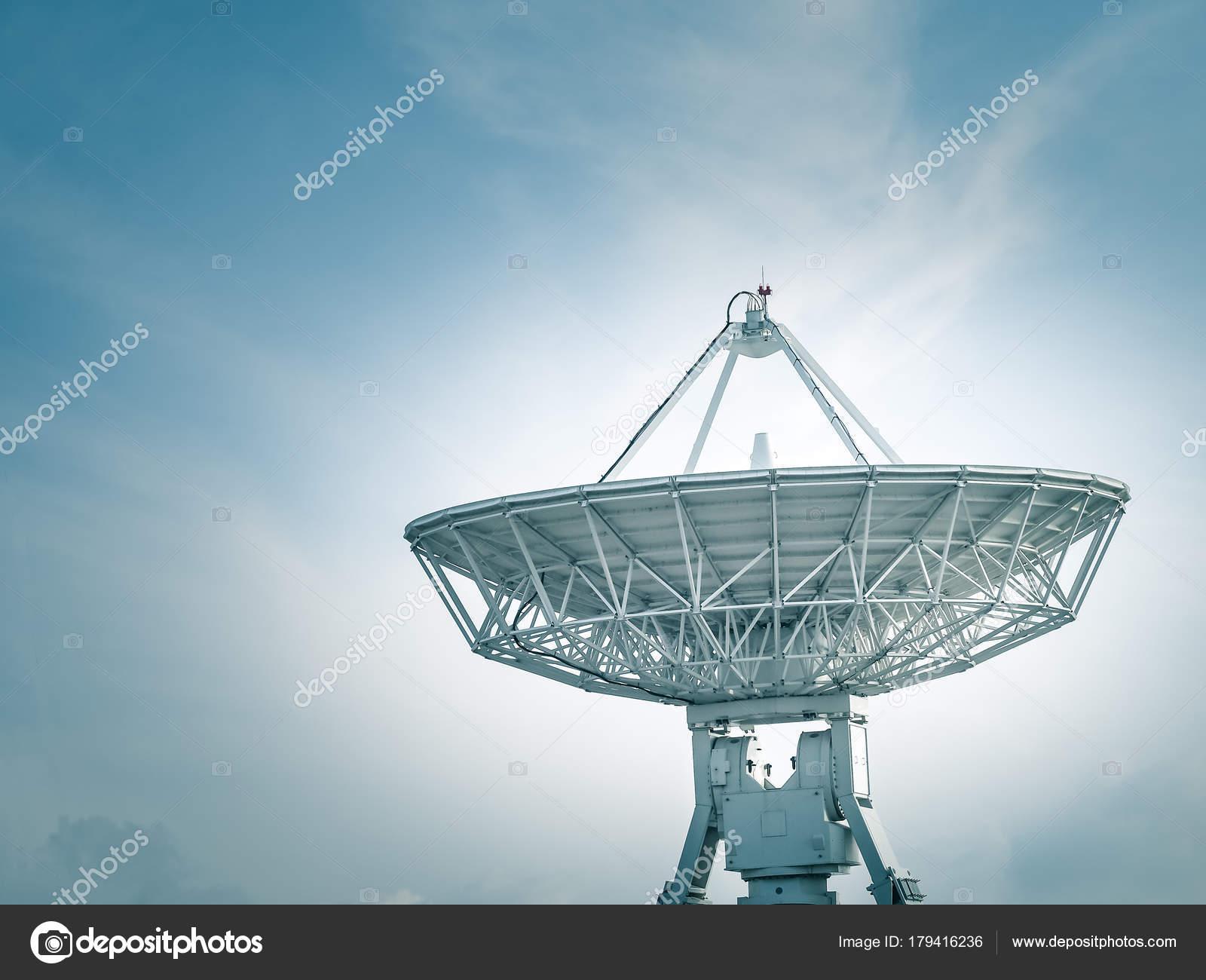 背景の青い空と地球局での衛星放...